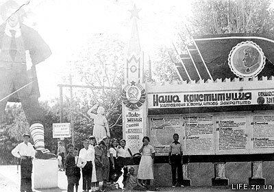 1938 год. Члены фотокружка у входа в Парк металлургов. Стенд с агитацией напоминает нам, что День Конституции в СССР до 1977 года отмечался 5 декабря.