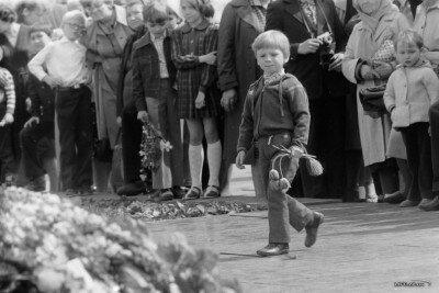 Мальчик несет цветы памятнику Ленина