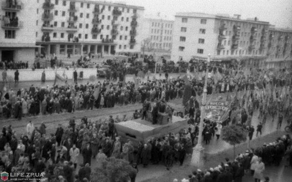 Ноябрь 1962 года. Колонны демонстрантов подходят к пл.Октябрьской. В просвете между жилыми домами ВШ №74.