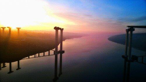 Солнышко встает над островом Хортица, новыми недостроенными мостами и Днепром.