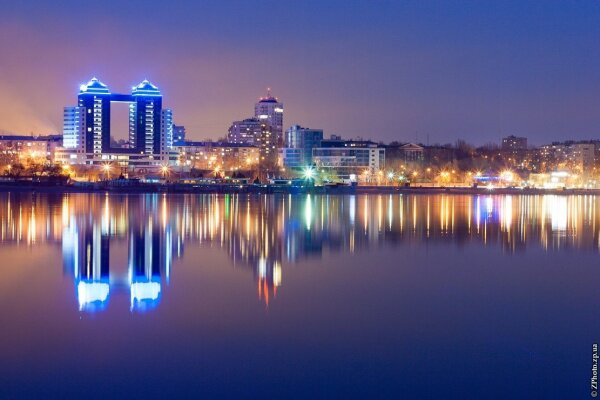 Вечерняя набережная отражается в спокойных водах Днепра