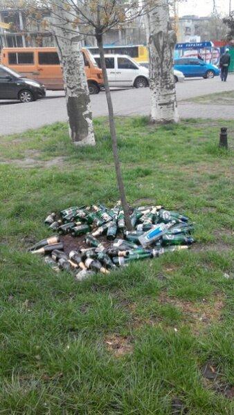 Куча бутылок под деревом