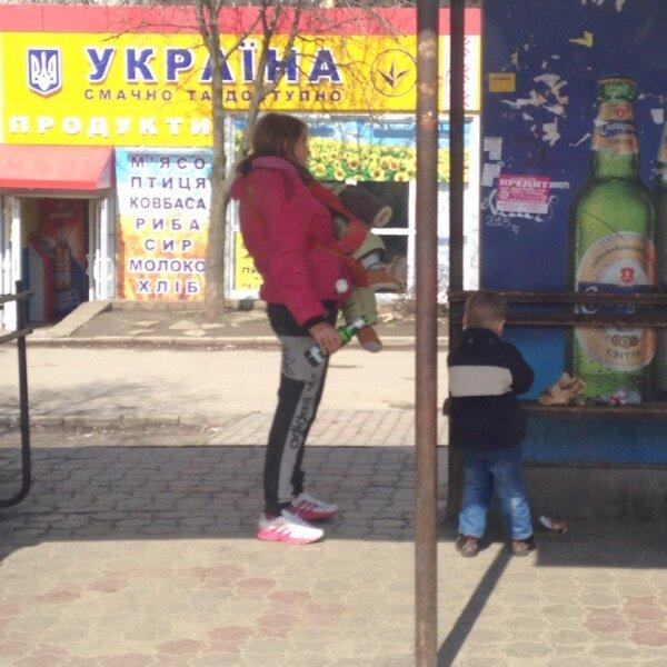 Молодая мама двоих детей на остановке с пивом