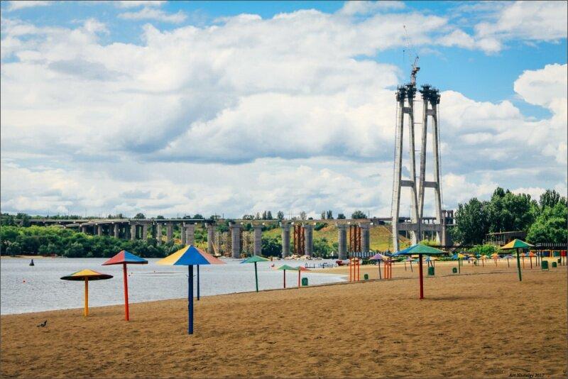 Разноцветные зонтики на плаже с видом на долгострой новых мостов